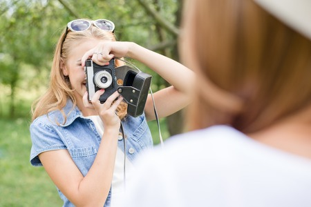 beautiful girl having fun taking photo of friend on green outdoors background photo