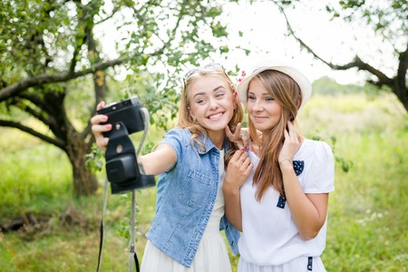 portrait of 2 beautiful young women having fun taking self photo on green outdoors background photo