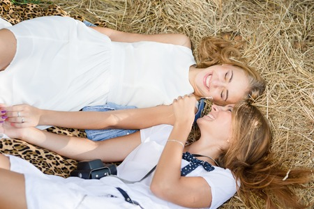 picture of relaxing lying on hay stack 2 beautiful young ladies having fun together photo