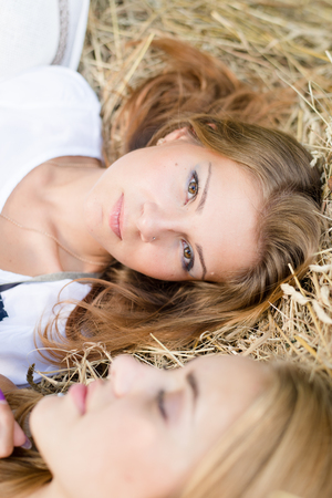 closeup picture of 2 beautiful young women best friends having fun relaxing lying on hay stack photo