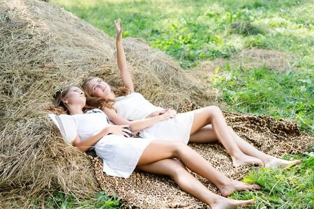 lying on hay stack 2 beautiful young women best friends having fun looking up photo