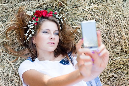 portrait of beautiful young lady having fun looking at mobile camera phone for making self picture photo