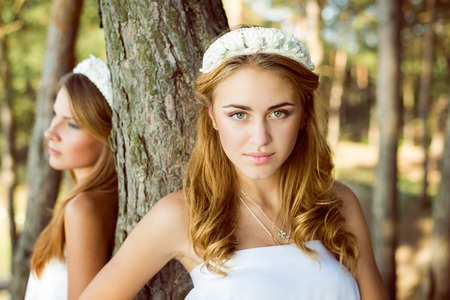 portrait of leaning on tree 2 beautiful princess young ladies in white dresses on summer outdoors photo