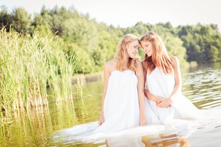2 beautiful princess young ladies in white dresses on summer water outdoors photo