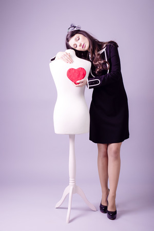 Young woman in classic black dress giving heart to mannequin studio background Stock Photo