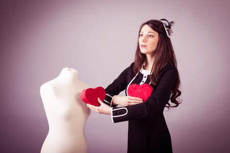 Young woman in classic black dress giving heart to mannequin studio background photo