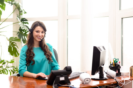 Young woman call centre operator speaking on headphones at work place with computer