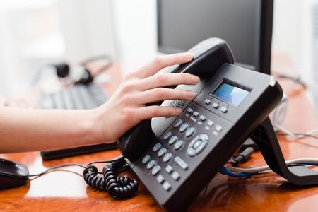 centro de computo: Cierre en tel�fono explotaci�n de la mano femenina en el escritorio de oficina Foto de archivo