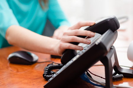 landline: Close up on female hand holding phone at office desk Stock Photo