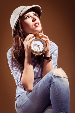 m�dula: Chica con sombrero de explorador y reloj de alarma sobre copia espacio fondo oscuro