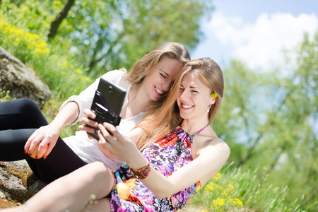 portrait of 2 beautiful young women having fun looking at tablet pc computer photo