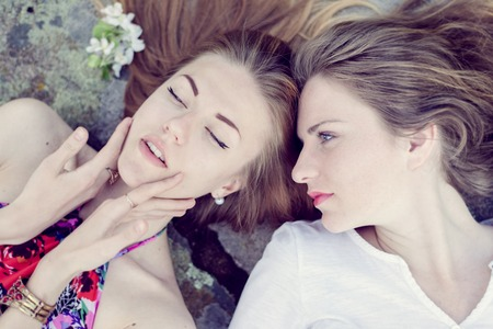 Closeup portrait of calm pretty girl friends lying down on stone abstract background photo