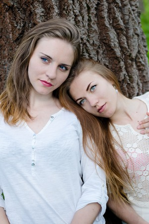 Portrait of calm pretty girl friends leaning against big tree on outdoors background photo