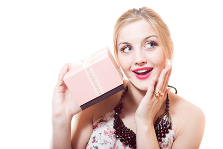 Beautiful sweet, sincere, gentle blond young woman holding wonderful gift in pink box isolated on white background