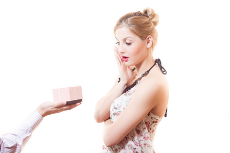 perplexity: Beautiful sweet, sincere, gentle blond young woman receiving wonderful gift in pink box from man