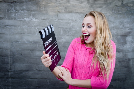 Happy young blond woman in pink knitted sweater with cinema clapper board smiling over brick wall copy space background photo