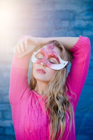 Sensual young blond woman wearing carnival mask over blue brick wall with sun flare copy space background Stock Photo
