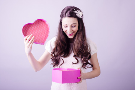 Portrait of beautiful young lady looking at love heart gift box photo