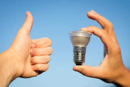LED lamp in hand and thumb up against blue sky photo