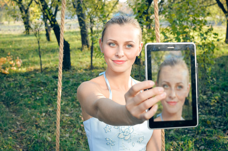 prom dress: Beautiful young woman in prom dress sitting on swings and making selfie on green summer or outdoors copyspace background Stock Photo