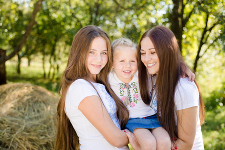 three sisters: Three sisters with small kid embracing on outdoors copy space background