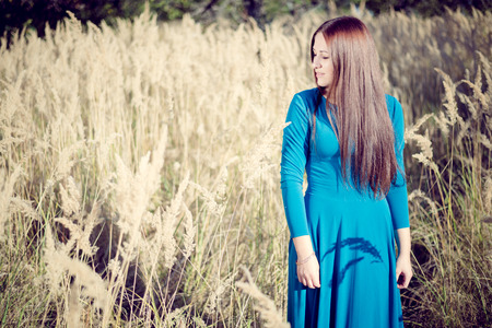 maxi dress: Beautiful girl in a blue dress on a background of nature