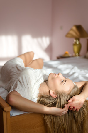 wellness sleepy: Young pretty woman in bed waking up and stretching