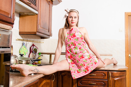 Portrait of young flexible beautiful lady wearing apron having fun in kitchen splitting legs apart