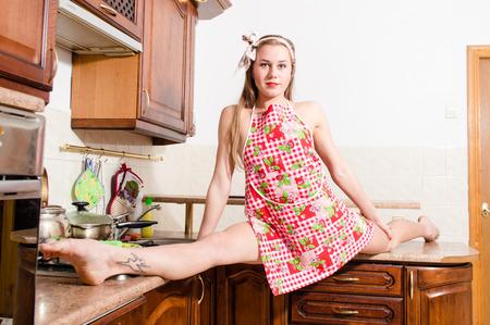 legs apart: Retrato de joven bella dama flexibles llevaba delantal que se divierte en la cocina piernas divisi�n aparte
