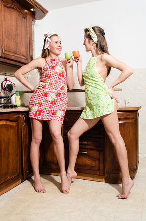 Two young sexy women in aprons with cups in kitchen photo