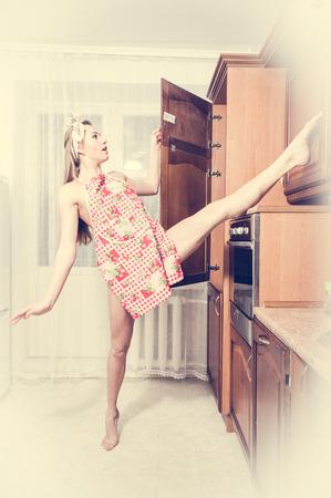 jambes �cart�es: Retro portrait de jeune souple belle dame portant un tablier en se amusant dans la cuisine jambes de se fendre