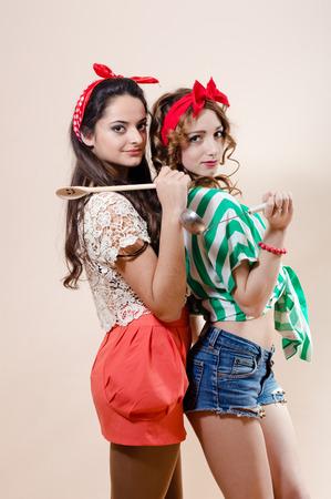 chicas divirtiendose: Retrato de dos hermosas chicas pin up que se divierten con utensilios de cocina Foto de archivo