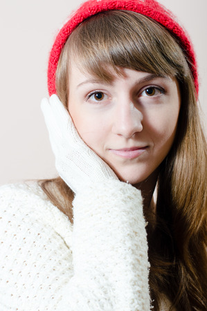 sensually: Young pretty woman wearing knitted red hat, white glove and jumper sensually looking at camera Stock Photo