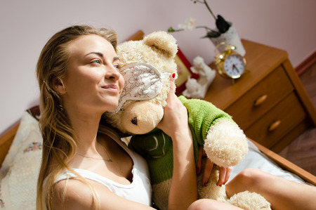 Hugging teddy bear young pretty woman happy smiling relaxing in bed photo