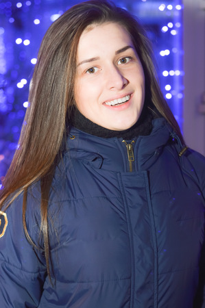 Portrait of beautiful young woman happy smiling on winter Christmas street lights and snow outdoors background photo