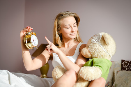time sensitive: Beautiful blond young woman on bed showing clock to her teddy bear