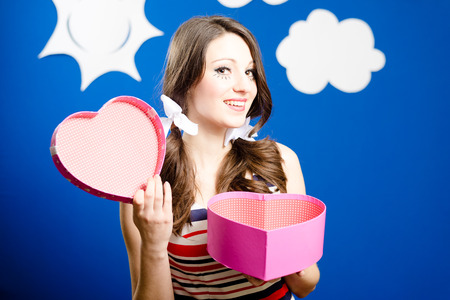 heart shaped: Smiling girl with heart shaped present box Stock Photo