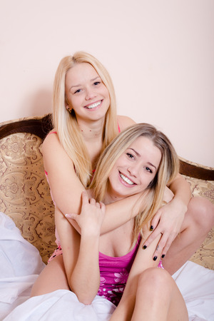 Portrait of hugging two sexy beautiful young women having fun sitting in bed wearing pajamas and happy looking at camera photo