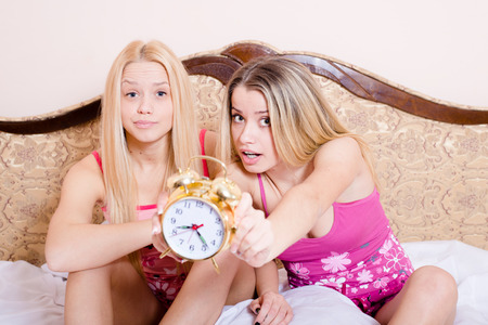 Portrait of two best girlfriends sitting in bed and showing clock photo