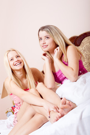 Two sexy beautiful young ladies having fun sitting in bed and happy smiling photo