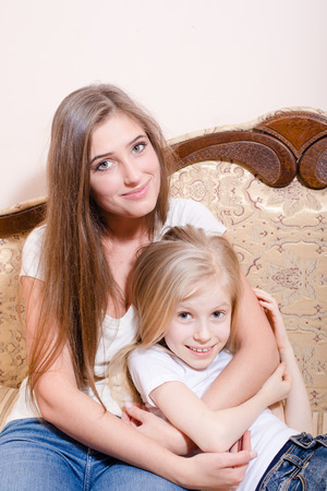 Picture of young pretty woman and little girl hugging together photo
