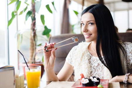 pretty lady: Young brunette pretty woman eating sushi in restaurant and happy smiling Stock Photo