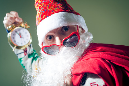 Portrait of Santa with heart shaped sun glasses holding clock showing five minutes to midnight photo