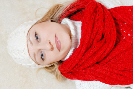Pretty young woman in knitted cap and red shawl lying over white fur background photo