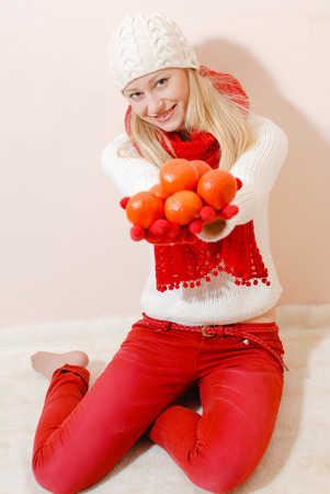 Pretty young woman in knitted cap and shawl holding pile of oranges photo