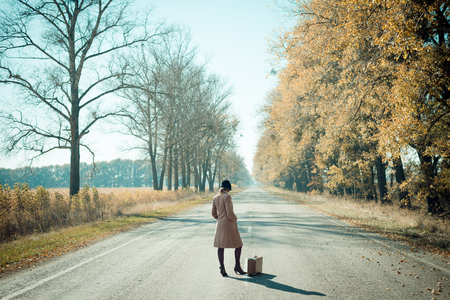 country girls: Woman with vintage suitcase hitchhiking on road