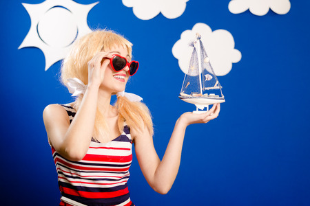 Funny woman in white wigg with sunglasses and toy ship in her hand photo