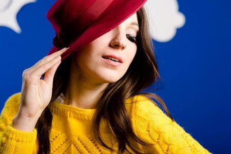 Fille au chapeau rouge dans le chandail jaune