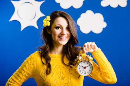Smiling girl with clock in yellow sweater photo