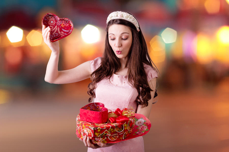 Portrait of beautiful surprised woman with red heart shaped present boxes on bokeh lights background photo